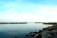 Smooth Adriatic sea surrounded by rocks under the azure sky royalty free stock photography