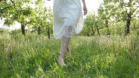 Smooth barefoot female legs walking on juicy grass stock video footage