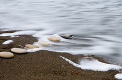 Beach pebbles and sea. Smooth beach pebbles in a row and sea waves. Concept of relaxing and calmness Stock Images