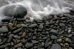 Smooth Beach Stones with Wave at Ocean Royalty Free Stock Images