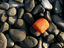 Smooth Black Rocks with One Orange Rock. Close-up of smooth, fist-sized black rocks with one orange rock for contrast Royalty Free Stock Photo