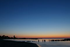 Smooth blue and orange sunset. Long exposure, smooth water effect, transition from blue to orange, some wooden poles in the horizon. A small lighthouse. The Royalty Free Stock Images