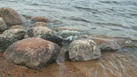 Smooth boulders polished by waves stock footage