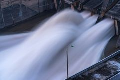 Smooth draining water from the hydroelectric dam at dawn.  royalty free stock photos