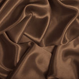 Smooth elegant brown silk or satin as background. In Sepia toned Royalty Free Stock Photos