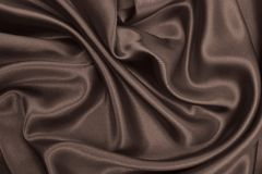 Smooth elegant brown silk or satin texture as abstract backgroun Stock Photos