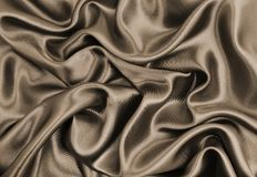 Smooth elegant brown silk or satin texture as abstract backgroun. Smooth elegant brown silk or satin texture can use as abstract background. Luxurious background Royalty Free Stock Image