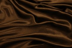 Smooth elegant brown silk or satin texture as abstract background. Luxurious background design. In Sepia toned. Retro style. Smooth elegant brown silk or satin royalty free stock photo