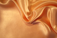 Smooth elegant golden silk as background Stock Photography