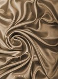 Smooth elegant golden silk or satin as background. In Sepia tone Stock Image