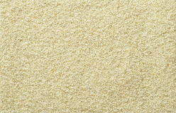 Smooth and even sand surface. Light brown and ocher colored grains of sand. Backgrounds. Closeup macro photo directly from above royalty free stock photography