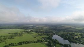 Smooth and fast flight over the lake and the village. Plain rural landscape. Sunny summer day. stock video