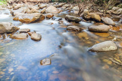 Smooth flowing water through natural rock creek. Stock Photo