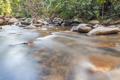 Smooth flowing water through the natural rock creek. Royalty Free Stock Photo
