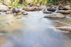 Smooth flowing water through the natural rock creek. Royalty Free Stock Images
