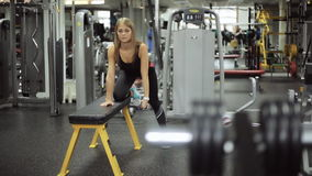 Smooth focus on a woman engaged in gym with dumbbells at bench. You can put right knee for example, if lean left hand on a horizontal bench. My right arm lean stock video