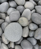 Smooth gray pebbles. Smooth gray stones with one almost circular one Royalty Free Stock Photos