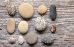 Smooth grey pebble on wood stock images