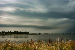 Smooth laminar storm clouds over a lake near Utrecht, The Netherlands. Calm before the storm. Beautiful cloud forms associated with a thunderstorm over the stock photos