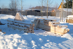 Smooth logs prepared for construction lying on snow Stock Image