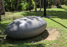 Smooth Marble Seat. Singapore - August 2016 - A smooth oval-shaped marble seat under the trees at the Gardens by the Bay royalty free stock photography