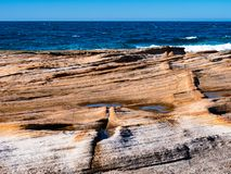 Smooth orange rocks and bright blue sea in Royal National Park in Sydney stock images