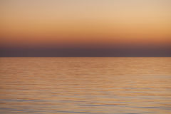 Smooth Orange Sea Sunset Background. Smooth Sea Sunset Texture background with pastel orange, red and yellow water and horizon royalty free stock image