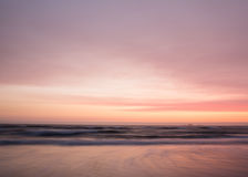 Smooth pastel colors of sunset over the ocean. A long exposure smooths waves and clouds in beach sunset of pastel pink and orange colors on the coast of stock photos