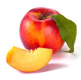 Smooth peaches and a half. And leaves on a white background Royalty Free Stock Images
