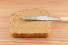 Smooth peanut butter being spread onto bread Stock Image