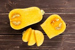 Smooth pear shaped orange butternut squash waltham on brown wood. Group of one half one quarter three slices of smooth pear shaped orange butternut squash stock image