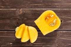 Smooth pear shaped orange butternut squash waltham on brown wood. Group of one quarter three slices of smooth pear shaped orange butternut squash waltham variety royalty free stock image