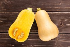 Smooth pear shaped orange butternut squash waltham on brown wood. Group of one whole one half of smooth pear shaped orange butternut squash waltham variety royalty free stock images