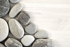 Smooth pebbles on an old wooden background. Stock Image
