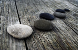 Smooth Pebbles on an Old Wooden Pier Royalty Free Stock Photography