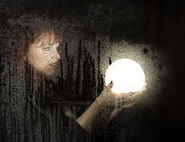 Smooth portrait of female model, posing behind transparent glass covered by water drops. woman holding large glowing Stock Photo
