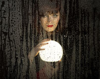 Smooth portrait of female model, posing behind transparent glass covered by water drops. woman holding large glowing Royalty Free Stock Photography