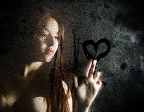 Smooth portrait of model, posing behind transparent glass covered by water drops and draws a heart on the glass Stock Photo