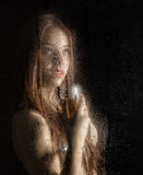Smooth portrait of sexy model, posing behind transparent glass covered by water drops. young woman holding a glass of Royalty Free Stock Photography