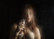 Smooth portrait of sexy model, posing behind transparent glass covered by water drops. young woman holding a glass of Stock Photography