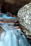 Smooth satin turquoise river with rocks in dark forest Stock Photos