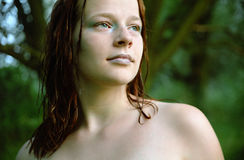 Smooth skin, wet hair. A young woman with wet red hair enjoying nature after a swim Stock Photos