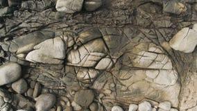 _ Smooth som glider surrskottet av stora stenar, vaggar och havsvatten på en ökust i Thailand stock video