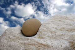 Smooth stone and rock. On blue sky and clouds Stock Photo