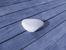 Smooth stone on wood Stock Photography