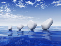 Smooth stones balanced on water Stock Images