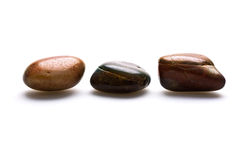 Smooth stones on white. A trio of three smooth stones on a white background royalty free stock image