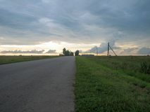Smooth straight asphalt road in the countryside under the sky with clouds at sunset royalty free stock images