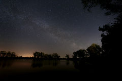 Smooth surface of forest lake on  background of the night sky a Stock Photo