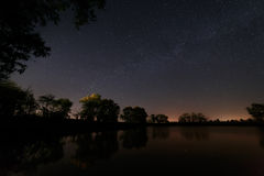 Smooth surface of forest lake on a background of the night sky Royalty Free Stock Photos